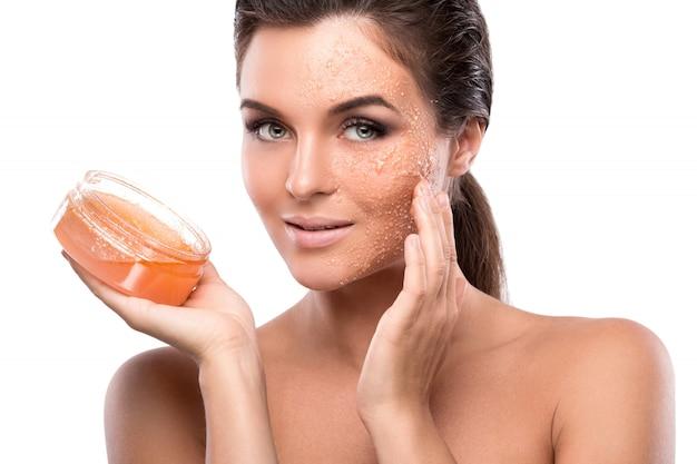 Belle jeune femme avec un gommage au sucre sur son visage