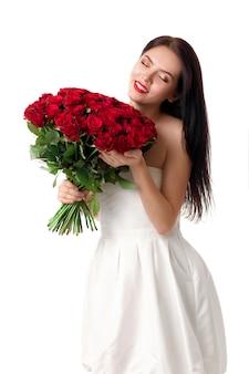 Belle jeune femme avec un grand bouquet de roses rouges