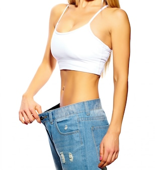 Belle jeune femme avec un gros jean, isolé sur blanc