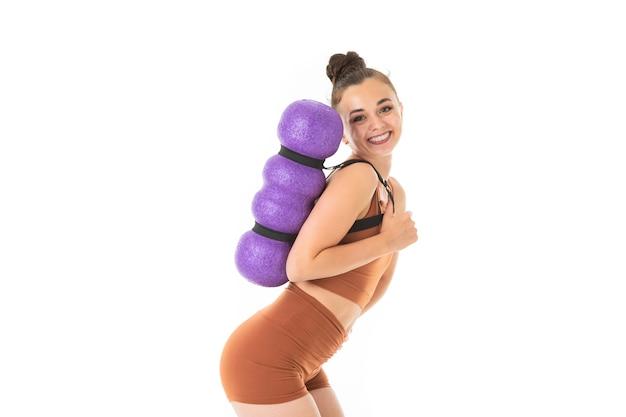 Belle jeune femme gymnaste aux cheveux longs noirs en peluche dans un paquet en costume élastique de sport marron fait avec l'inventaire sportif