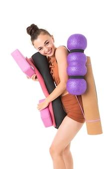 Belle jeune femme gymnaste aux cheveux longs noirs en peluche dans un paquet en costume élastique de sport marron avec inventaire sportif
