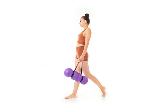 Belle jeune femme gymnaste aux cheveux longs noirs en peluche dans un paquet en costume élastique de sport marron marche avec l'inventaire sportif