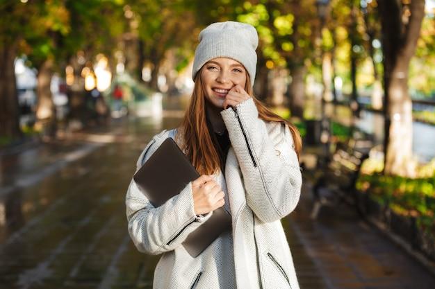 Belle jeune femme habillée en manteau d'automne et chapeau marchant à l'extérieur, transportant un ordinateur portable