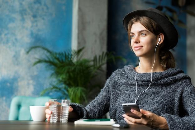 Belle jeune femme habillée en pull et chapeau assis dans une chaise à la table du café, écouter de la musique avec des écouteurs, intérieur élégant, prendre des notes