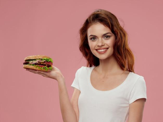 Belle jeune femme avec un hamburger juteux dans ses mains, une femme mangeant un hamburger