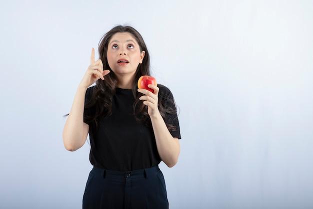 Belle jeune femme en haut noir tenant une pomme fraîche.