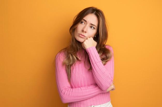 Belle jeune femme en haut rose regardant de côté avec une expression pensive pensant