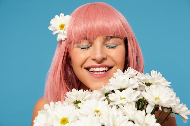 Belle jeune femme heureuse avec des cheveux roses courts portant du maquillage de fête tout en posant dans des fleurs blanches, souriant agréablement les yeux fermés