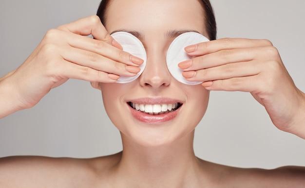 Belle jeune femme heureuse close-up avec des tampons de coton dans les deux mains près des yeux avec un sourire blanc comme neige sur le