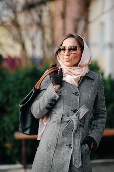 Belle jeune femme heureuse dans un manteau posant dans le parc