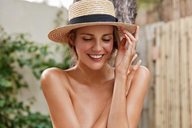 Belle jeune femme heureuse avec des dents blanches, une peau douce et saine, porte un chapeau de paille, regarde vers le bas avec une expression joyeuse, passe des vacances d'été dans un pays tropical. concept de personnes, de beauté et de soins