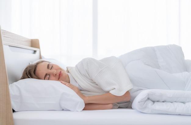 Belle jeune femme heureuse de dormir confortablement dans son lit