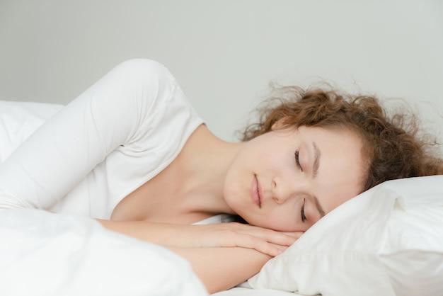 Belle jeune femme heureuse de dormir et dormir profondément dans son lit