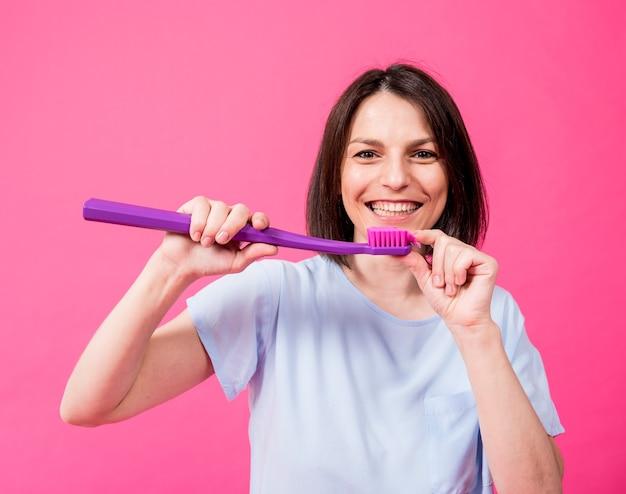 Belle jeune femme heureuse avec une grosse brosse à dents sur fond rose blanc