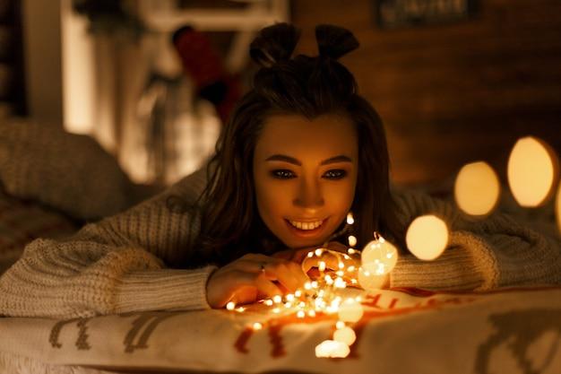 Belle jeune femme heureuse avec des lumières de noël dans un pull vintage tricoté sur le lit