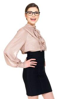 Belle jeune femme heureuse à lunettes et chemise beige avec jupe noire- isolé sur fond blanc