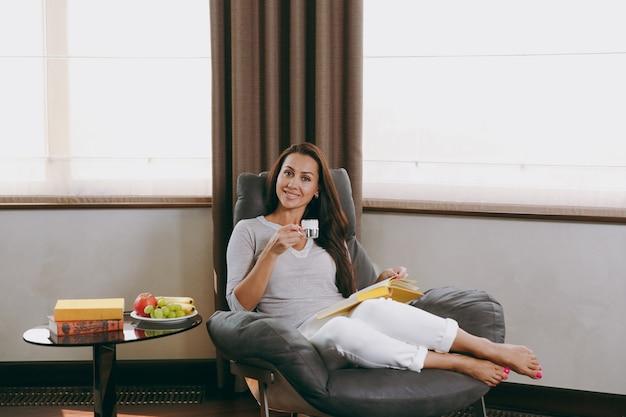 La belle jeune femme heureuse à la maison assise sur une chaise moderne devant la fenêtre, se relaxant dans son salon, lisant un livre et buvant du café ou du thé