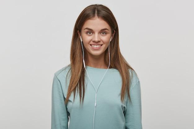 Belle jeune femme heureuse avec maquillage naturel et cheveux bien coiffés, sourires
