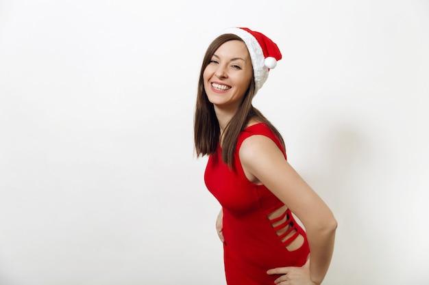 Belle jeune femme heureuse de race blanche avec un sourire charmant portant une robe rouge et un chapeau de noël sur fond blanc. portrait isolé de santa girl. concept de vacances de nouvel an 2018. regarder la caméra.