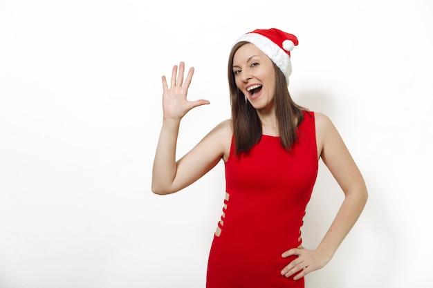La belle jeune femme heureuse de race blanche avec un sourire charmant portant une robe rouge et un chapeau de noël montrant les pouces cinq sur fond blanc. portrait isolé de santa girl. concept de vacances de nouvel an 2018
