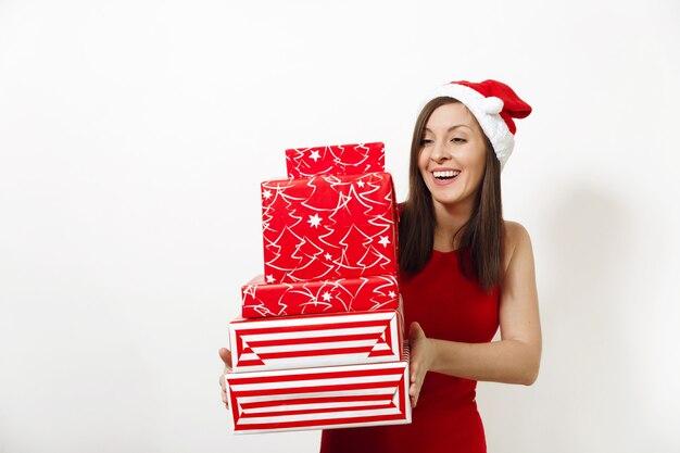 Belle jeune femme heureuse de race blanche avec un sourire charmant vêtue d'une robe rouge et d'un chapeau de noël tenant des coffrets cadeaux sur fond blanc. fille de santa avec présent isolé. concept de vacances de nouvel an 2018