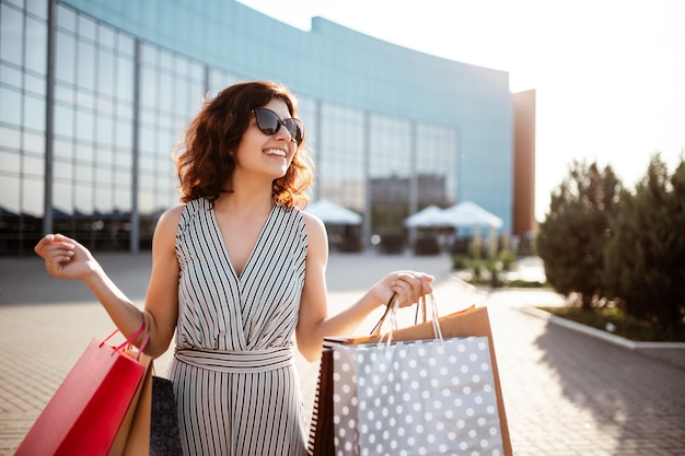 Belle jeune femme heureuse sort du centre commercial avec des achats.