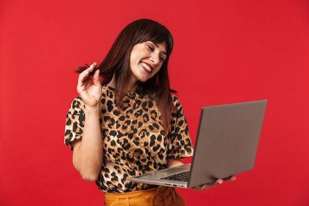 Belle jeune femme heureuse vêtue d'une chemise imprimée d'animaux posant isolée sur un mur rouge à l'aide d'un ordinateur portable.