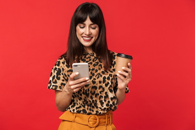 Belle jeune femme heureuse vêtue d'une chemise imprimée d'animaux posant isolée sur un mur rouge buvant du café à l'aide d'un téléphone portable.
