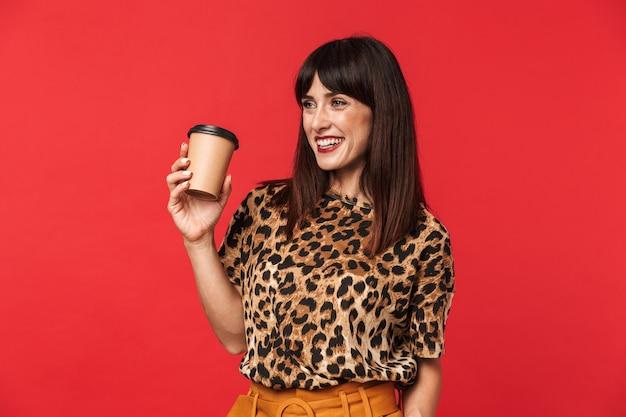 Belle jeune femme heureuse vêtue d'une chemise imprimée d'animaux posant isolée sur un mur rouge buvant du café.