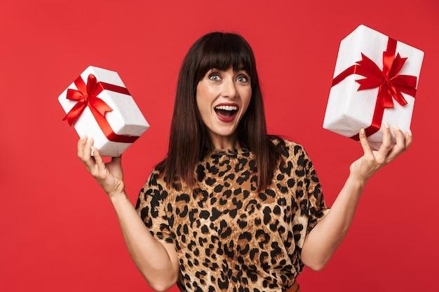 Belle jeune femme heureuse vêtue d'une chemise imprimée d'animaux posant isolée sur un mur rouge tenant une boîte présente.