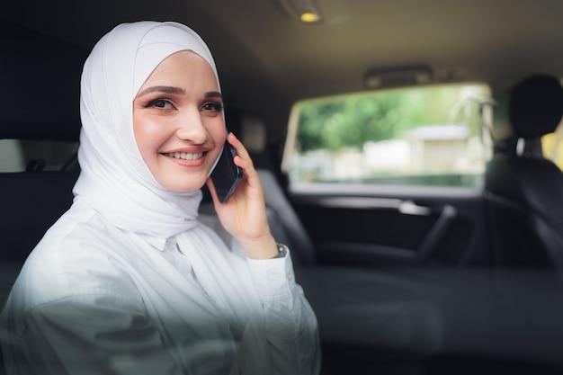 Belle jeune femme en hijab assise dans une voiture et parlant au téléphone