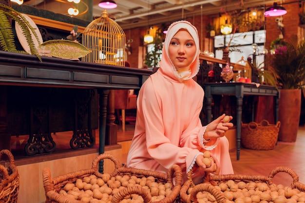 Belle jeune femme avec un hijab rose.