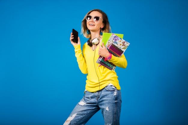 Belle jeune femme hipster tenant des livres et regardant smartphone