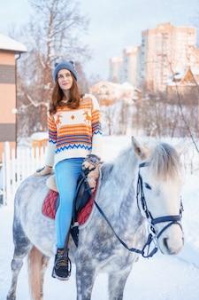 Belle jeune femme en hiver avec beau cheval blanc