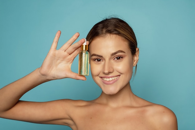 Une belle jeune femme hydrate sa peau avec un sérum