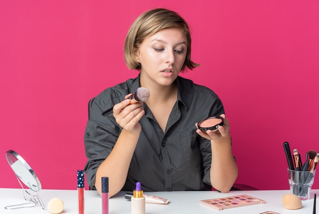 Une belle jeune femme impressionnée est assise à table avec des outils de maquillage tenant un pinceau à poudre et regardant un fard à joues en poudre dans sa main