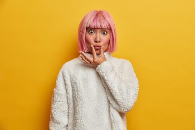 Une belle jeune femme impressionnée fait la moue et regarde avec des yeux écarquillés, fait la grimace, a les cheveux teints en rose, les joues rouges et une peau saine
