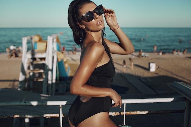 Une belle jeune femme incroyable sexy en maillot de bain noir et lunettes de soleil posant sur la plage. cheveux longs, bikini noir, mode, fil rouge