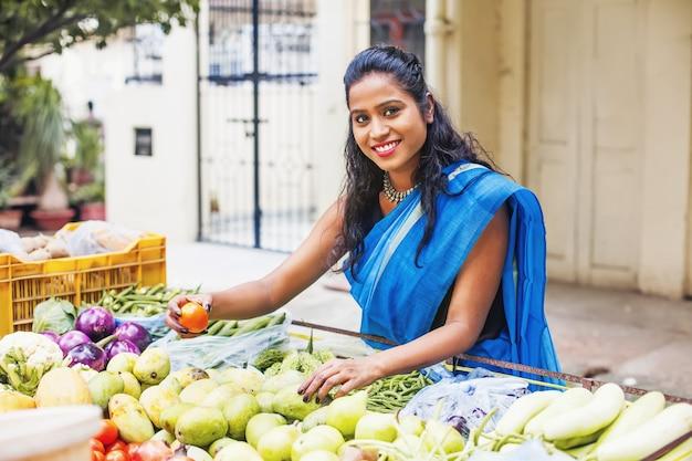 Belle jeune femme indienne dans un sari achetant des tomates d'un étal de légumes