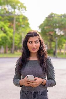 Belle jeune femme indienne pensant tout en utilisant le téléphone dans les rues du parc