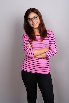 Belle jeune femme indienne portant des lunettes contre le mur gris