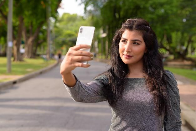 Belle jeune femme indienne prenant selfie dans les rues du parc