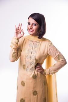 Belle jeune femme indienne en tenue traditionnelle montrant le signe ok
