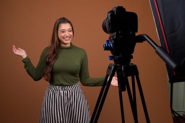 Belle jeune femme indienne vlogging contre mur marron