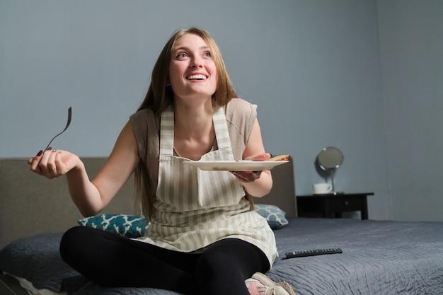 Belle jeune femme avec intérêt à regarder la télévision et à manger, femme assise sur le lit avec des aliments frais faits maison, avec télécommande, se détendre à la maison