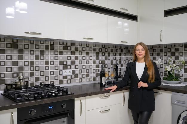 Belle jeune femme à l'intérieur de cuisine moderne de luxe noir et blanc avec un design épuré