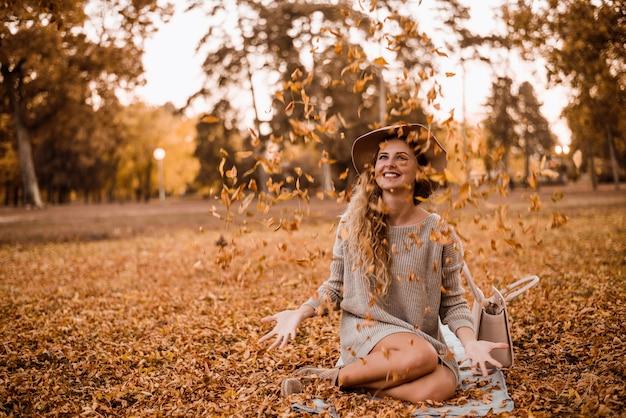 Belle jeune femme jetant les feuilles jaunes en l'air.