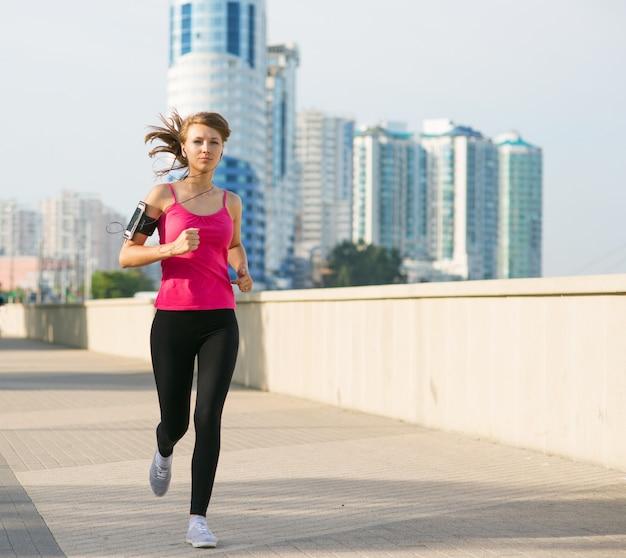 Belle jeune femme sur un jogging matinal dans la ville en écoutant de la musique dans les écouteurs du smartphone fixé dans sa poche sur le bras