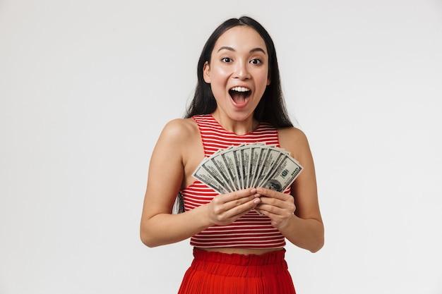 Belle jeune femme jolie asiatique posant isolé sur mur blanc tenant de l'argent.