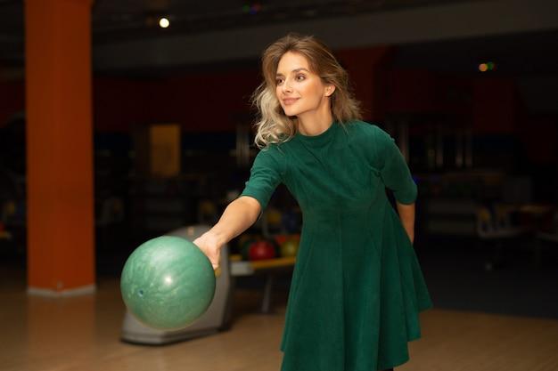 Belle jeune femme jouant au bowling